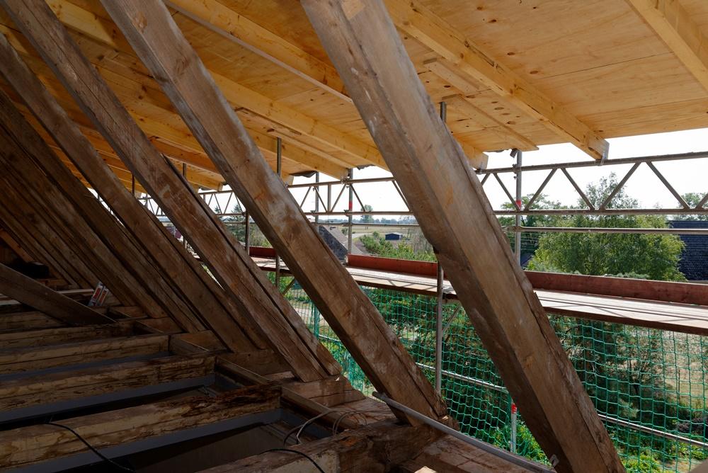 Schutzdach für die Zeit der Sanierung - Blick auf marode Dachbalken